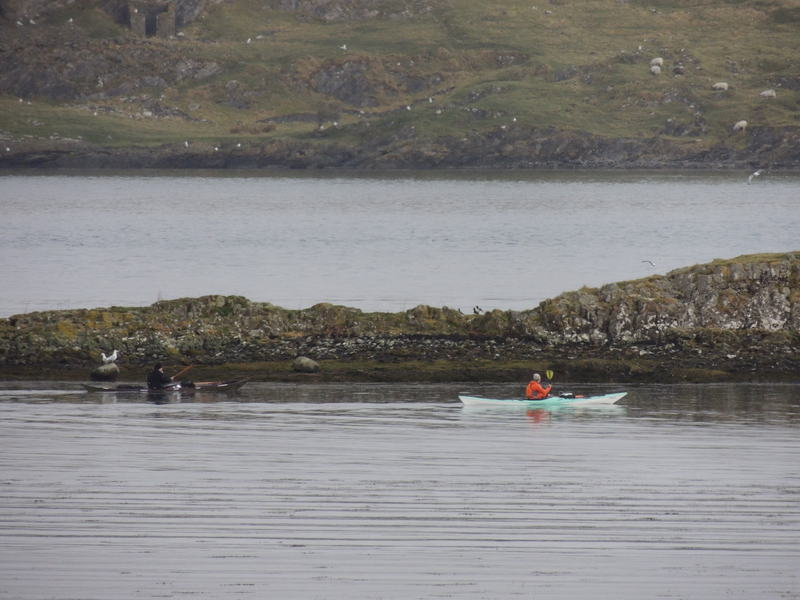 Early Sunday morning Kayaker moving around rocks opposite cottages